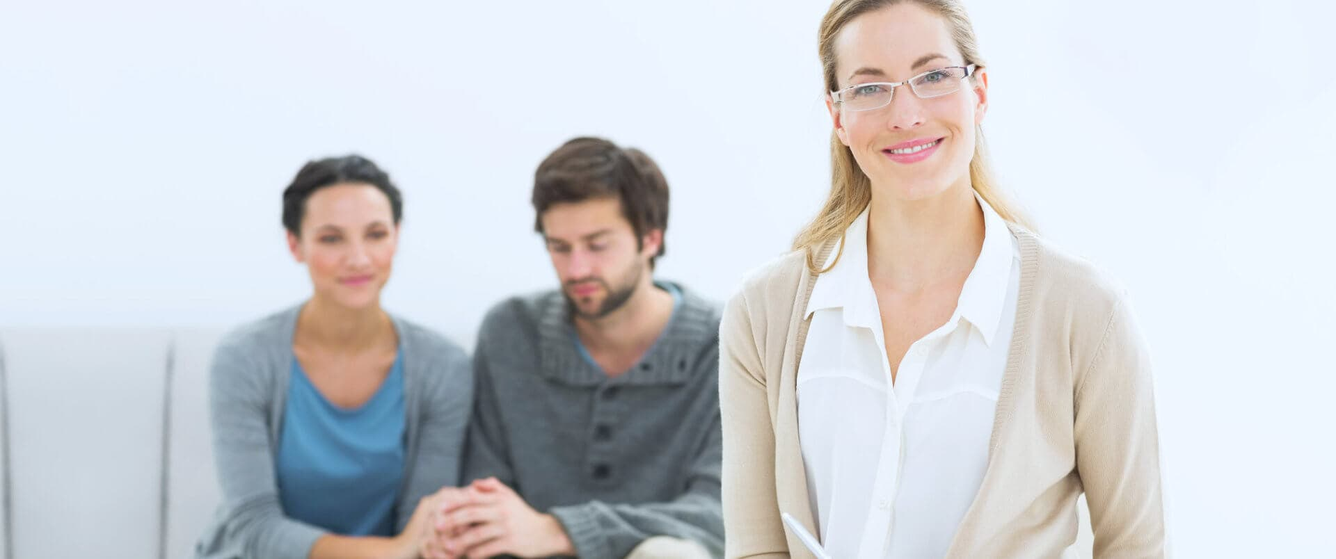 therapist smiling with couple at the backgroun