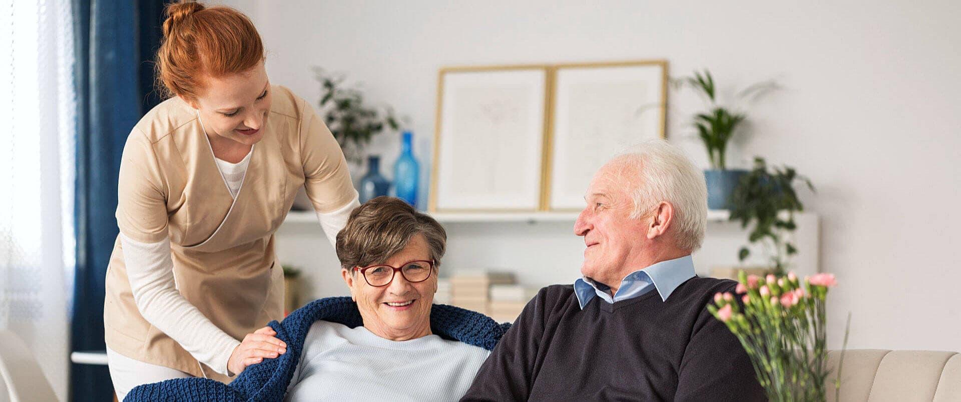 caregiver putting blanket at senior woman and senior man smiling