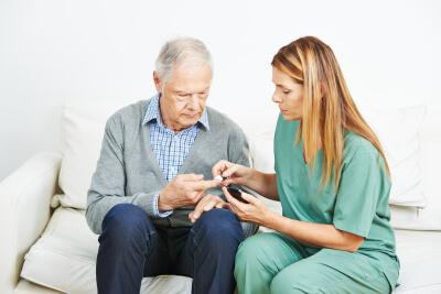 caregiver taking senior's blood sugar